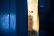 A prisoner stands behind his cell door window that has 'Bye' graffitied on it.<br /> HMP/YOI Portland, a resettlement prison with a capacity for 530 prisoners. Dorset, United Kingdom.