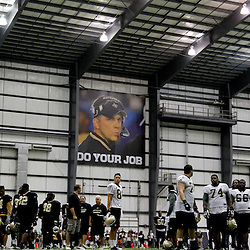 July 27, 2012; Metairie, LA, USA; A sign of New Orleans Saints head coach Sean Payton who was suspended by NFL commissioner Roger Goodell is seen over players following a training camp practice at the team's indoor practice facility. Mandatory Credit: Derick E. Hingle-US PRESSWIRE