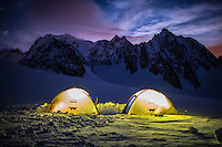 An wide angle view on two yellow tents, illuminated by headtorches, with the summit of Mont Blanc visible against starry winter sky.