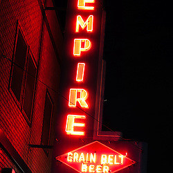 """Picture of Empire Tavern and Liquors neon sign at night in Fargo, North Dakota.  The rustc old bar sign also says """"Grain Belt Beer""""."""