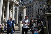 A muscular young man checks messages below the classical architecture of Royal Exchange and the WW1 war memorial at Bank Triangle, on 10th May 2017, in the City of London, England.