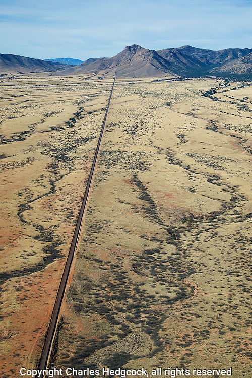 Aerial photograph, looking West.The Normandy style border fence between Arizona, USA & Sonora, Mexico, as it terminates into the eastern slope of the Huachuca Mountains.