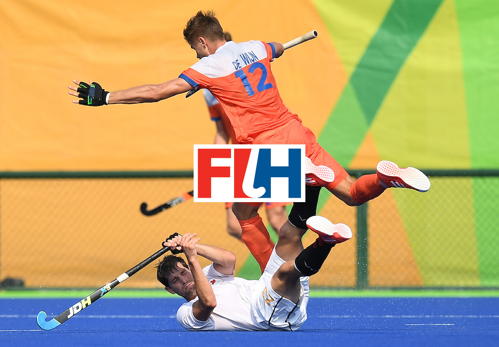 Netherland's Sander de Wijin trips over Canada's Iain Smythe (bottom) during the men's field hockey Netherlands vs Canada match of the Rio 2016 Olympics Games at the Olympic Hockey Centre in Rio de Janeiro on August, 9 2016. / AFP / MANAN VATSYAYANA        (Photo credit should read MANAN VATSYAYANA/AFP/Getty Images)