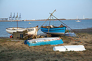 Fishing boats on beach Port of Felixstowe in distance, Harwich, Essex,