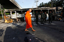 A monk walks past a burnt bus at a Thai army line on a road leading to Government House in Bangkok, Thailand, 14 April 2009.  Thai soldiers prepare to crack down on anti-government protesters gathered outside Government House in Bangkok in a major escalation of political violence in the kingdom. Thai Prime Minister Abhisit Vejjajiva declared a state of emergency in Bangkok to quell anti-government protests that forced the cancellation of the ASEAN summit in Pattaya.