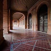 An image of geometry- a long corridor in the Plaza de Espana. Seville, Spain
