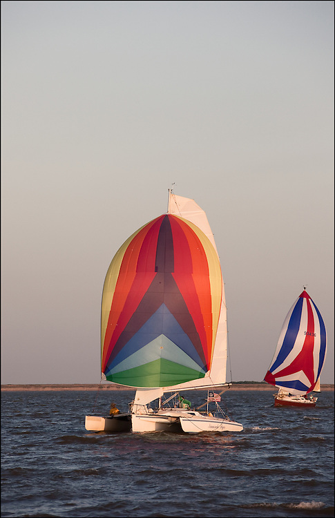 Colorful mainsails on multiple sailboats in the waters of Cheney Lake..