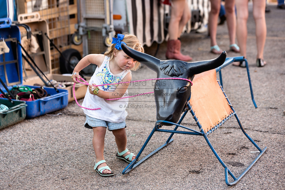 A young girl tries her hand a roping a play steer during Cheyenne Frontier Days July 25, 2015 in Cheyenne, Wyoming. Frontier Days celebrates the cowboy traditions of the west with a rodeo, parade and fair.
