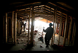 1 June, 2006. Lakeview, New Orleans, Louisiana. The first day of hurricane season 2006. Illegal Mexican immigrant workers gut a marina boat house on Breakwater Drive which backs onto the New Orleans Marina. The workers wait at gas stations early in the mornings in the hope they will be picked up by contractors. Few speak any English and all send money back to their families in Mexico every week.