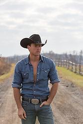 All American rugged cowboy on a dirt road