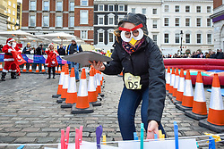 © Licensed to London News Pictures. 07/12/2019. LONDON, UK.  7 December 2019.  A participant dressed as a penguin takes part in The 39th Great Christmas Pudding Race in Covent Garden, raising funds for Cancer Research as well as having lots of festive fun.  Photo credit: Stephen Chung/LNP