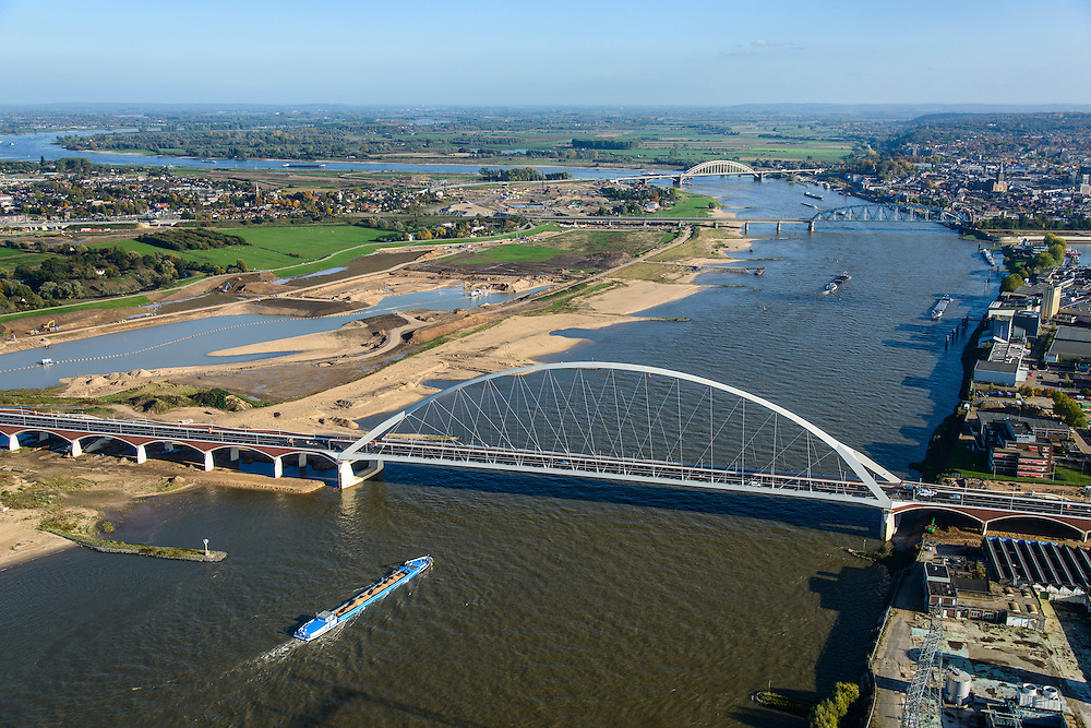 Nederland, Gelderland, Nijmegen, 24-10-2013; de nieuwe stadsbrug van Nijmegen over rivier de Waal, De Oversteek. Daarachter de spoorbrug met fietspad (De Snelbinder) en de laatste brug is de Waalbrug. Links van de rivier grondwerkzaamheden voor de Dijkteruglegging Lent (Ruimte voor de Rivier). Links Nijmegen-Noord, rechts binnenstad.<br /> First bridge the new city bridge of Nijmegen on the river Waal, De Oversteek (The Crossing). Next the railway bridge with cycle path De Snelbinder (The Luggage strap) and finally the Waal bridge. To the left of the river groundwork for the Dike relocation of Lent (project Ruimte voor de Rivier: Room for the River). Nijmegen city on the horizon.luchtfoto (toeslag op standaard tarieven);<br /> aerial photo (additional fee required);<br /> copyright foto/photo Siebe Swart.
