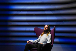 """© Licensed to London News Pictures. 29/10/2019. LONDON, UK. A staff member poses with """"Big Brother Diary Room Chair, Series 1"""", 2000, courtesy Alan Davies and """"Big Brother Series 2 Logo"""", 2001, by Daniel Eatock. Preview of """"24/7: A Wake-Up Call For Our Non-Stop World"""", a new exhibition opening on 31 October at Somerset House.  The show examines our inability to switch off from our 24/7 culture.  Over 50 multi-disciplinary works explore the pressure to produce and consume information around the clock. taking visitors on a 24-hour cycle from dawn to dusk through interactive installations.  Photo credit: Stephen Chung/LNP"""