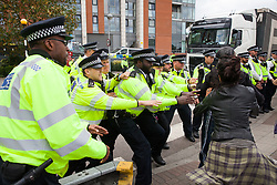 London, UK. 3 September, 2019. Several Metropolitan Police officers prevent two female activists from blocking a road in front of a truck arriving at ExCel London on the second day of a week-long carnival of resistance against DSEI, the world's largest arms fair. The second day's events were organised around a theme of No Faith In War and were attended by representatives of many faith groups including a significant number of Quakers.
