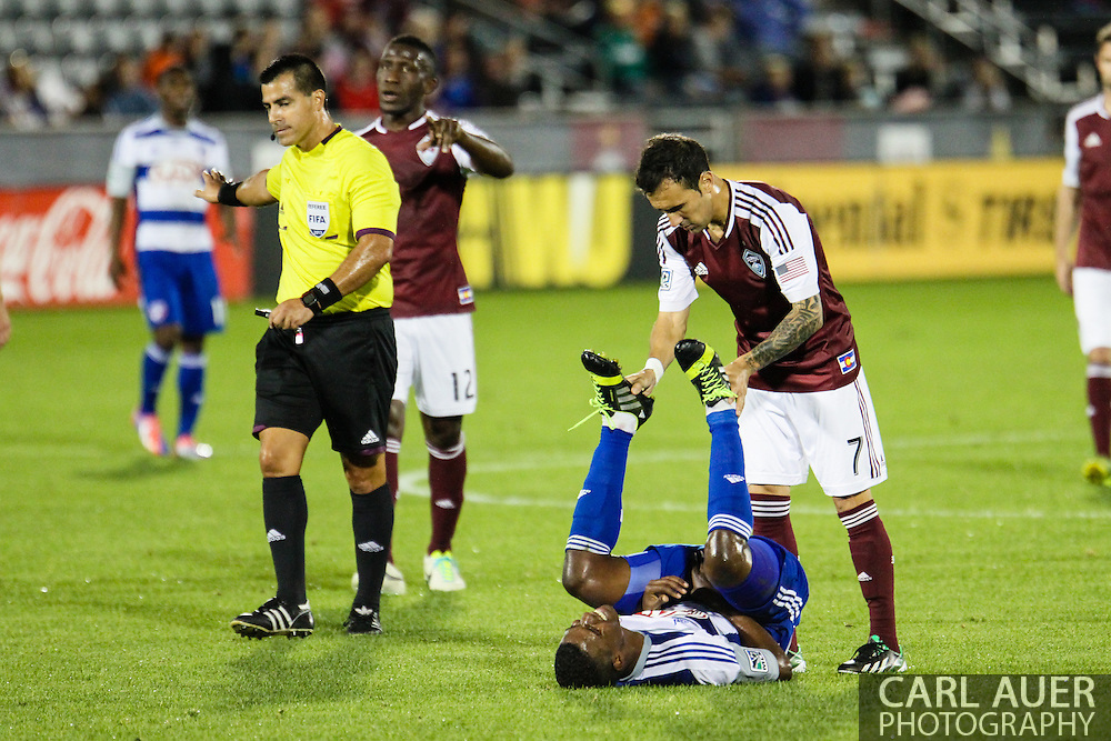 September 14th, 2013 -  In a goodwill gesture, Colorado Rapids forward Vicente Sánchez (7) helps FC Dallas midfielder Erick (12) recover from a pulled muscle in the first half of action in the MLS Soccer game between FC Dallas and the Colorado Rapids at Dick's Sporting Goods Park in Commerce City, CO