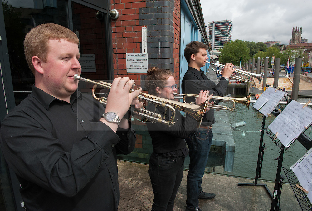 """© Licensed to London News Pictures. 27/07/2015. Bristol, UK.  """"Fanfare for Bristol"""", titled """"At the Top of the Tide"""", composed by David Mitcham, commissioned by Bristol Proms 2015, performed live for the Mayor of Bristol, George Ferguson and Artistic Director of the Bristol Old Vic, Tom Morris for the first time at Bristol's famous Temple Mead train station, heralding the opening of the Bristol Proms 2015.  David Mitcham's  """"At the Top of the Tide"""" was inspired by 'Bristol's inextricable links to the sea'.  The first performance by Arc Brass took place outside the Engine Shed, and throughout the day, performances took place at the Watershed, Pero's Bridge, the Wills Memorial Bell Tower and finally at Bristol Old Vic itself. David Mitcham, who has worked extensively for the BBC Natural History Unit based in Bristol said: """"I am thrilled that my Fanfare """"At the Top of the Tide"""" has been chosen for the city of Bristol and to open Bristol Proms 2015. I hope the Fanfare represents the rich diversity of Bristol, its maritime and industrial heritage as well as being a celebration of the spirit of the city and the energy it will carry into the future.""""  Bristol Proms 2015 runs from today, 27th July to 1st August and features some of the world's finest musicians including Alison Balsom, Miloš Karadaglić, Pumeza Matshikiza and Daniel Hope.  Photo credit : Simon Chapman/LNP"""