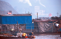 CHINA SICHUAN PROVINCE FENGDU MAY99 - Chinese women wash their clothes in the Yangtse river against the backdrop of a factory in the background. Seven large cities and thousands of villages will be submerged once the water level rises after the completion of the controversial Three Gorges Dam project further downriver. The flooding of areas reaching back more than 550Km upriver will require the evacuation and resettlement of more than 10 million people.  jre/Photo by Jiri Rezac. © Jiri Rezac 1999. . Contact: +44 (0) 7050 110 417. Mobile:  +44 (0) 7801 337 683. Office:  +44 (0) 20 8968 9635. . Email:   jiri@jirirezac.com. Web:     www.jirirezac.com