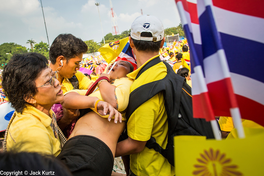 05 DECEMBER 2012 - BANGKOK, THAILAND: A woman who fainted in the heat is helped by members of the crowd on the Royal Plaza Wednesday. She fainted while waiting to see Bhumibol Adulyadej, the King of Thailand, before his public audience at the Mukkhadej balcony of the Ananta Samakhom Throne Hall. December 5 is a national holiday. It's also celebrated as Father's Day. Celebrations are being held across the country to mark the birthday of Bhumibol Adulyadej, the King of Thailand.    PHOTO BY JACK KURTZ