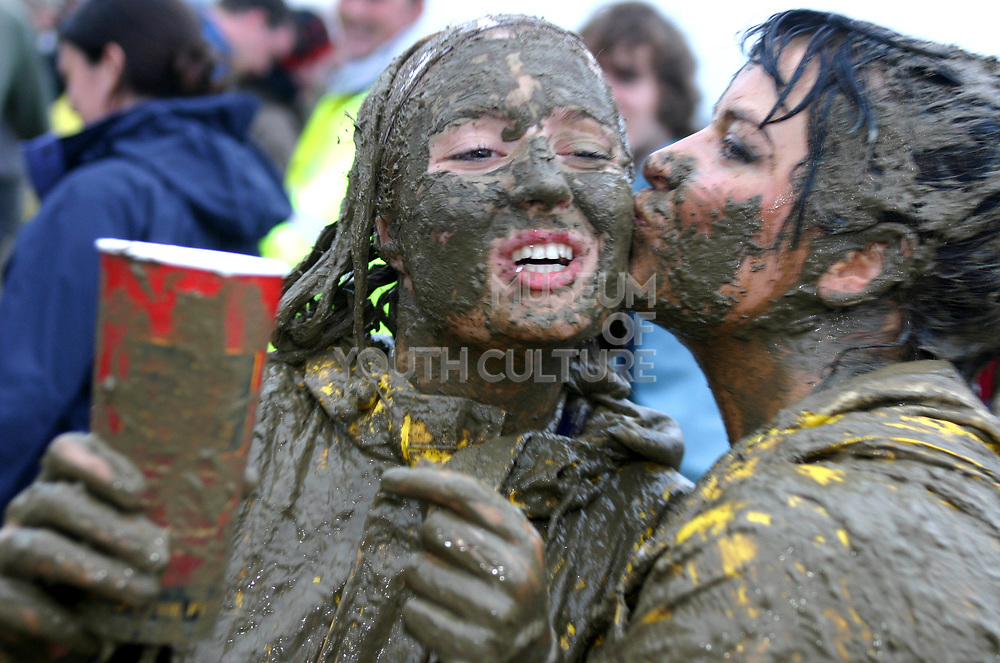 Two girls covered in mud, one kissing the other, Glastonbury 2005