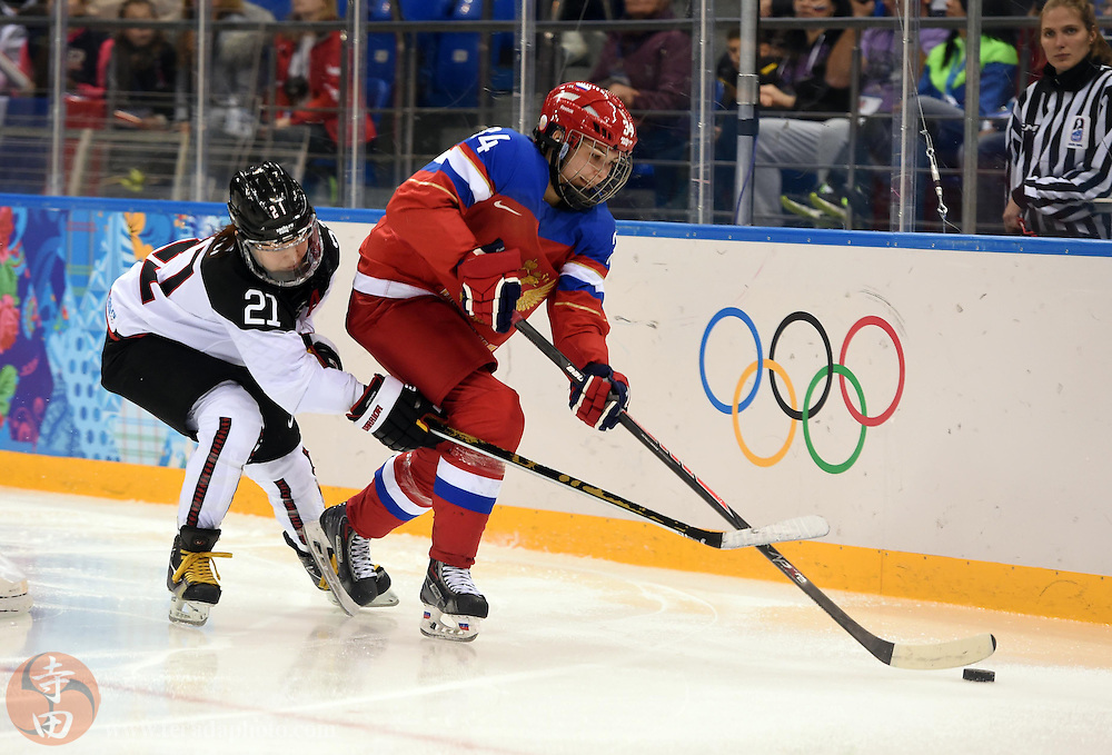 Feb 16, 2014; Sochi, RUSSIA; Russia defenseman Svetlana Tkachyova (34) controls the puck ahead of Japan forward Hanae Kubo (21) in a women's ice hockey classifications round game during the Sochi 2014 Olympic Winter Games at Shayba Arena.