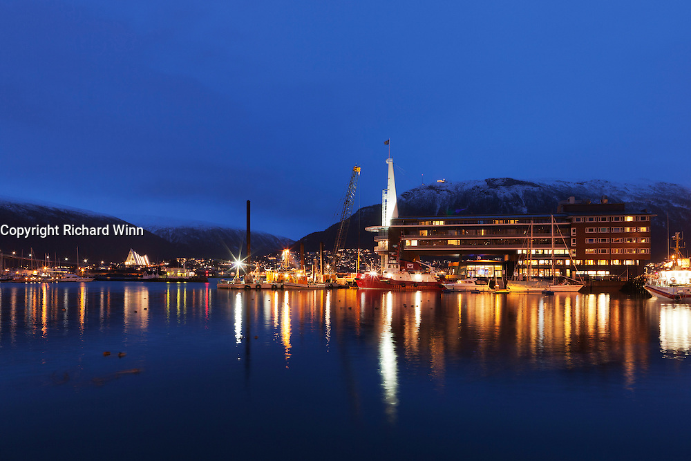 Night view of part of the harbour area of Tromsø, showing the Ishavshotel and Ishavskatedralen (The Arctic Cathedral).