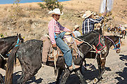 A young boy rides along with Mexican cowboys on the road up Cubilete Mountain on the final leg of the annual Cabalgata de Cristo Rey pilgrimage January 5, 2017 in Silao, Guanajuato, Mexico. Thousands of Mexican cowboys and horse take part in the three-day ride to the mountaintop shrine of Cristo Rey.