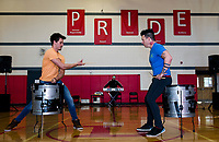 Ryan Vezina challenges Justin Spencer to a drum duel during Recycled Percussion's surprise visit to Laconia Middle School on Monday afternoon.  (Karen Bobotas/for the Laconia Daily Sun)