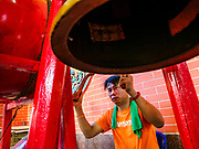 04 SEPTEMBER 2017 - BANGKOK, THAILAND: A man bangs a prayer gong during a food distribution at Chaomae Thapthim Shrine. About 1,000 people came to the shrine for the annual food distribution. Staples, like rice and cooking oil, are donated to the shrine throughout the year and donated to poor people from the communities around the shrine. Food distributions like this are a tradition at Chinese shrines in Bangkok and a common way of making merit for the people who donate the staples.     PHOTO BY JACK KURTZ