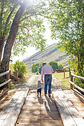 Toddler and father hold hands walking towards the sunset on a wooden bridge under some trees against the backdrop of Wyoming mountains.