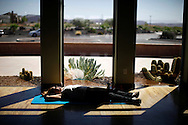 A guest in the stretch class lies in the sun in one of the workout rooms at the Biggest Loser Resort in Ivins, Utah September 6, 2010.  The resort affiliated with the popular reality television show is typically booked 5 to 6 months in advance.  REUTERS/Rick Wilking (UNITED STATES)