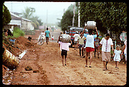 Boys carry propane tanks, used throughout Brazil for cooking, down muddy Eirunepe main street. Brazil