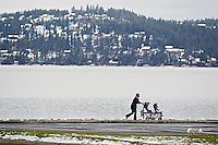 Erin Zasada pushes her children in a stroller along the beach Friday at Independence Point in downtown Coeur d'Alene..