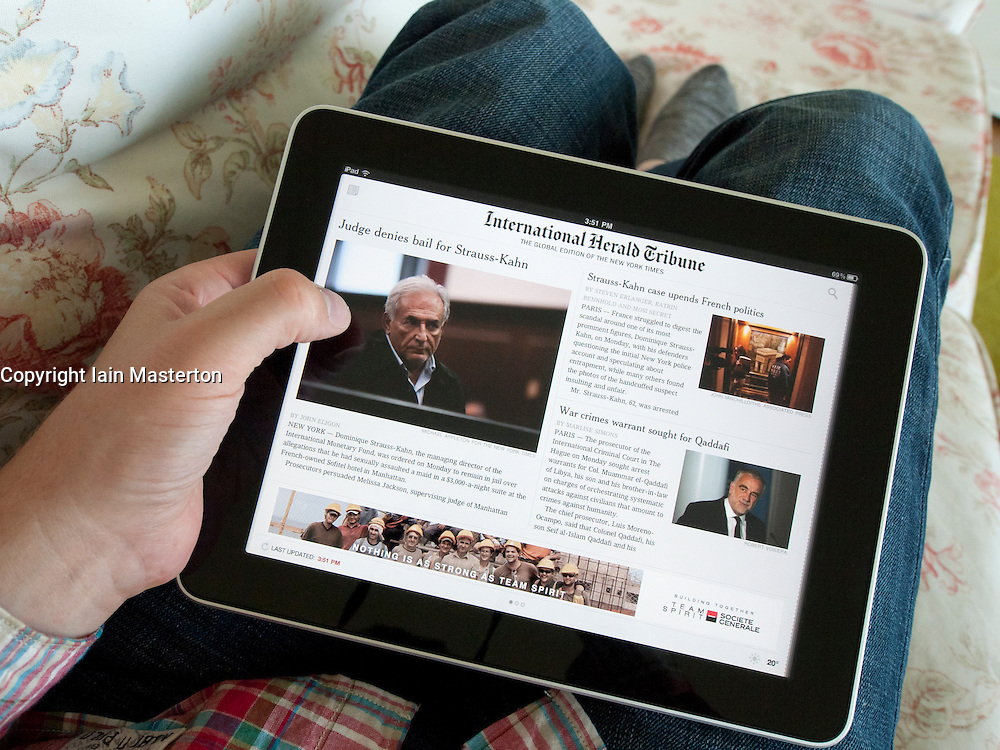 Reading digital subscription edition of International Herald Tribune on an iPad touch screen tablet computer