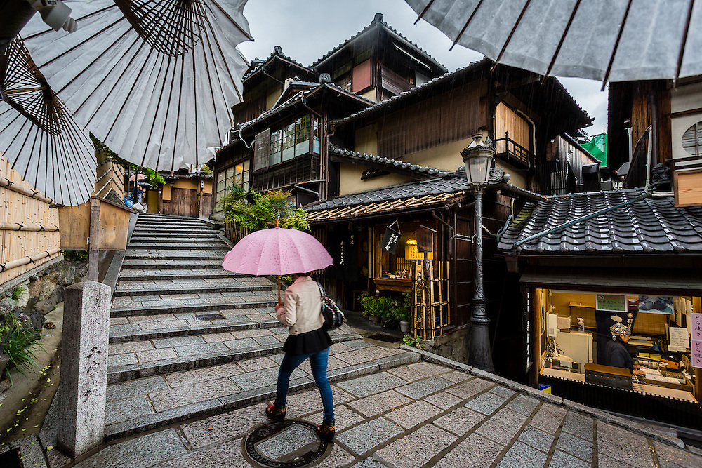 A woman with a pink umbrella passes by a shop front near Ninenzaka stairs.