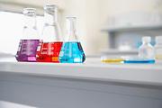 Beakers of multi-coloured liquid in laboratory