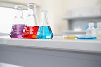 Beakers of multi-coloured liquid in laboratory