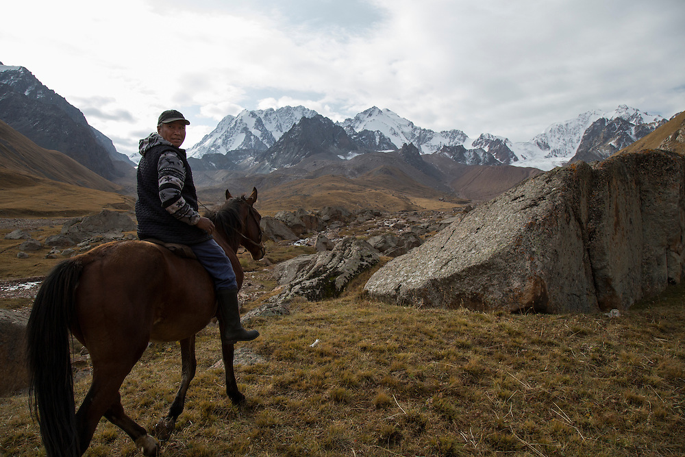 Nurdin Orozaliev rides towards the glaciers that lie at the base of Chok Tal.