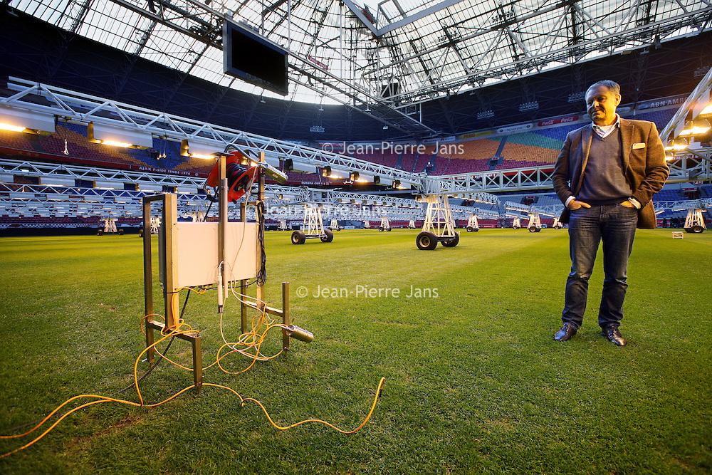"""Nederland, Amsterdam , 24 november 2014.<br /> Als eerste stadion ter wereld zet de Arena een z.g. robot (links in beeld) aan het werk om de gesteldheid van het gras te monitoren.<br /> Op de foto Henk van Raan in het stadion naast de """"grasrobot""""<br /> Henk van Raan Henk is Board Member of the Amsterdam ArenA and specializes in facility and project management, preparation of project plans, maintenance concepts and planning.He manages the sustainability program which results in a carbon neutral stadium in 2015.<br /> Foto:Jean-Pierre Jans"""