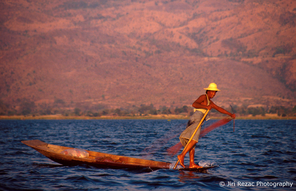 BURMA SHAN STATE INLE LAKE MAR95 - A fisherman casts his net in the traditional and unique 'leg-rowing' style, a technique involving the use of one arm and one leg, thus leaving the other arm free for fishing. This technique is native to fisherman on the Inle Lake and is not known to be practiced anywhere else in the world. .. jre/Photo by Jiri Rezac. . © Jiri Rezac 1995. . Contact: +44 (0) 7050 110 417. Mobile: +44 (0) 7801 337 683. Office: +44 (0) 20 8968 9635. . Email: jiri@jirirezac.com. Web: www.jirirezac.com