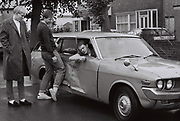 Three friends with car which has been in an accident, London, UK, 1983