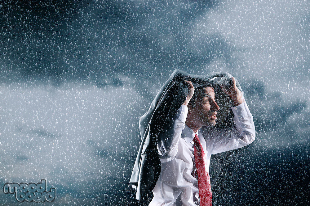 Businessman covering head with jacket during rainstorm