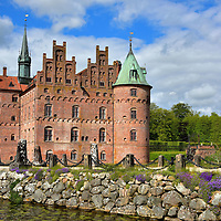 Narrow Path Leading to Egeskov Castle in Kværndrup, Denmark <br /> This narrow path across the moat leads towards some wonderful visual treasures. Architect lovers will enjoy the amazing construction of the Egeskov Castle which includes 66 rooms and 2,062 panes of window glass.  Equally amazing is Titania's Palace, an enormous doll house that contains over 3,000 intricate components. It took 15 years to build this home for the imaginary fairies that lived in the castle's garden. The young of heart will also enjoy the exhibit of paper cutouts from the 1800s by fairytale author Hans Christian Andersen.