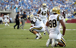 UCLA offensive lineman Scott Quessenberry (52) and Takkarist McKinley (98) react after failing to score on fourth down in overtime against Texas A&M during a NCAA college football game Saturday, Sept. 3, 2016, in College Station, Texas. Texas A&M won 31-24 in overtime. (AP Photo/Sam Craft)