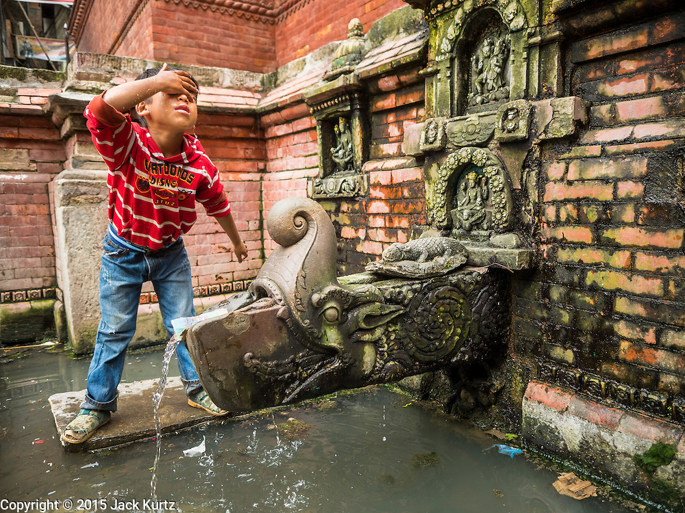 01 AUGUST 2015 - KATHMANDU, NEPAL:  A boy washes his face with water from a public well in a community near Durbar Square in Kathmandu. Many homes in the area don't have domestic water and people still go to wells for their water. The earthquake in April, 2015, badly damaged infrastructure, including the water system, in this part of town.      PHOTO BY JACK KURTZ