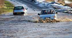 © Licensed to London News Pictures. 27/01/2013..Cleveland, England, UK..Following the recent snowfall a fast thaw through the night brought heavy flooding to some parts of Cleveland and North Yorkshire with many roads closed...A car drives through flood water on a road near to Boulby in East Cleveland...Photo credit : Ian Forsyth/LNP