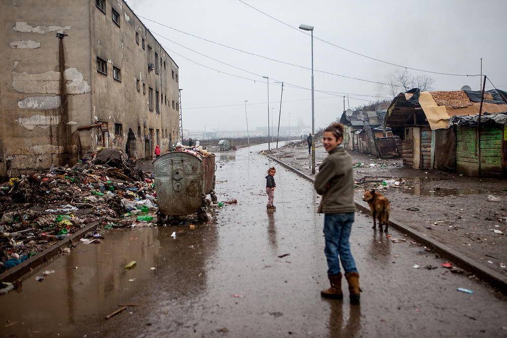 """The main road at the segregated Roma settlement """"Budulovska Street"""" (2016). In 2015 the """"muddy"""" roads to and in the settlement were asphalted and the infrastructure for the residents  improved. The city has roughly 11200 inhabitants, about 1980 (18%) of them have Roma ethnicity and around 800 are living at the segregated settlement 'Budulovska Street' (2014)."""