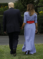U.S. President Donald Trump and First Lady Melania Trump leave after attending a picnic for military families in Washington, D.C., U.S., on Wednesday, July 4, 2018. Dozens of retired military and national security officers joined the NAACP and the American Medical Association in urging a federal appeals court to uphold a court order blocking Trump's ban on transgender people serving in the military. Photographer: Yuri Gripas/Bloomberg