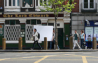 Two women carying a large white board along the street in Dublin, Ireland.