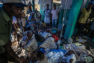 RENDEL, HAITI - OCTOBER 12, 2016:  The small clinic in Rendel, Haiti is overflowing with Cholera patients, and more keep coming. For days, aid groups and officials have warned of a coming Cholera outbreak that could affect as many as 500,000 Haitians.  The town of Rendel and its surroundings, which once sheltered 25,000 people, is an epicenter of the coming disaster. Heroic nurses care for patients splayed on the floor like silent rag dolls, some resting atop the improvised stretchers they arrived on. Patients vomit and defecate on the floor or into small yellow buckets, too sick to leave their stifling confines. The smell of bile and excrement stings the nostrils.