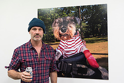 "© Licensed to London News Pictures. 28/03/2018. LONDON, UK.  Glaswegian street photographer Dougie Wallace stands in front of one his images from his new book ""Well Heeled"", a book about dogs.  Preview of ""The Series"", an exhibition by Dougie Wallace at Bermondsey Project Space from 27 March to 14 April.  Works on display are from diverse subjects such as the mega-rich in Harrodsburg, Shoreditch, Blackpool as well as his latest project ""Well Heeled"", a street photography book with dogs as the subject.  Photo credit: Stephen Chung/LNP"